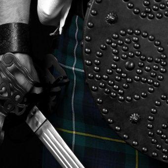 Highlander with basket hilt sword and targe wearing Campbell tartan kilt (round studded shield)