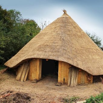 A reconstructed round building with a cone top